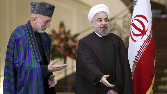 Iran's President Hassan Rouhani, right, stands with Afghan President Hamid Karzai, before their meeting at Tehran's Saadabad Palace in Iran, Sunday, Dec. 8, 2013. Karzai arrived in Tehran for a one-day visit on Sunday to discuss regional and international issues with Iranian officials. (AP Photo/Ebrahim Noroozi)