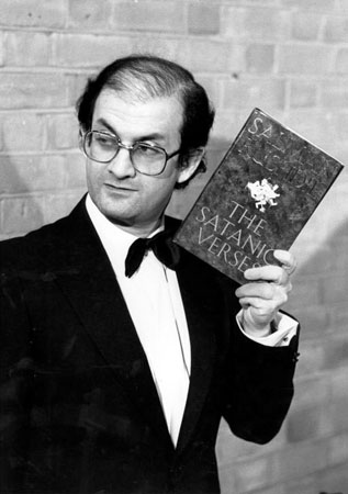 Salman Rushdie holding a copy of his book The Satanic Verses