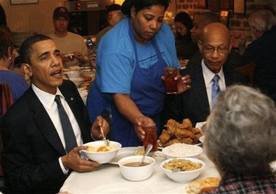 President Barack Obama makes a comment to reporters about his cholesterol level as he passes a plate while siting down with other customers as he visits Mrs. Wilkes' Dining Room in Savannah, Ga., Tuesday, March 2, 2010. At right is Savannah Mayor Otis Johnson. (AP Photo/Charles Dharapak)
