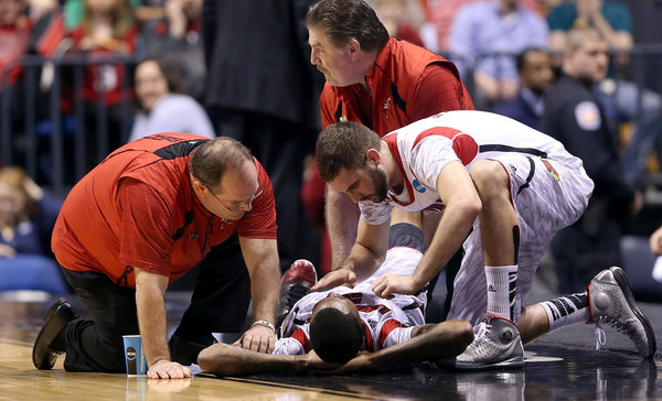 Louisville captain Luke Hancock comforted Kevin Ware after he broke his leg in last week's N.C.A.A. Midwest Regional final game against Duke. Andy Lyons/Getty Images