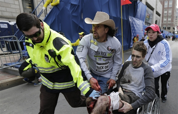 Carlos Arredondo helps a victim of the Boston Marathon bombings on Monday. Photo:  Charles Krupa / AP