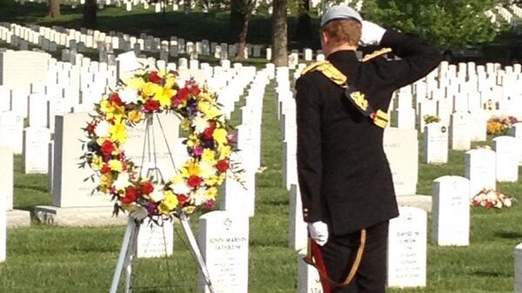 The prince salutes a wreath laid at the gravestone of a US soldier