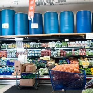 BIN OVER THEIR HEADS: Pioneer Supermarket in Brooklyn sells plastic barrels that customers use to ship food to family members in the Caribbean. Photo J.C. Rice