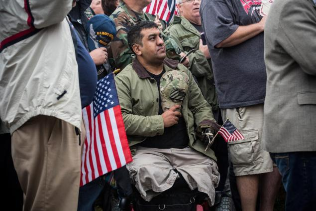A man in a wheel chair recites the Pledge of Allegiance at a rally centered around reopening national memorials closed by the government shutdown.