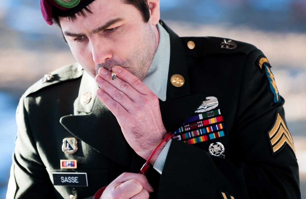 Sgt. Paul Sasse smokes a cigarette while in handcuffs Feb. 12 outside a courtroom at Fort Carson as he waits to be arraigned on assault charges. Sasse, who did three combat tours, went back to the El Paso County jail, still without charge, after the hearing was canceled. Michael Ciaglo / The Gazette