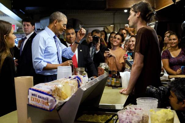 Never leave home without it: President Obama scrutinizes his credit card while ordering barbecue at Franklin Barbecue in Austin, Texas, Thursday. (AP Photo/Jacquelyn Martin)
