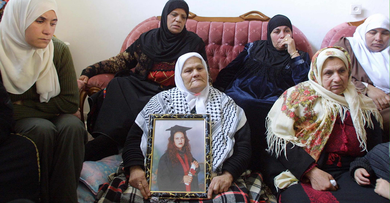 Wasfiyeh Idris, the mother of suicide bomber Wafa Idris, surrounded by other female family members, holds a portrait of her daughter at her home in the al-Amari refugee camp near the West Bank town of Ramallah 30 January, 2002. Idris believed to be the first ever female Palestinian suicide bomber, blew herself up in central Jerusalem 27 January, killing an elderly Israeli man in an attack claimed by the al-Aqsa Martyrs' Brigades, a radical offshoot of Palestinian leader Yasser Arafat's Fatah movement.        AFP PHOTO/Awad AWAD [Photo via Newscom]