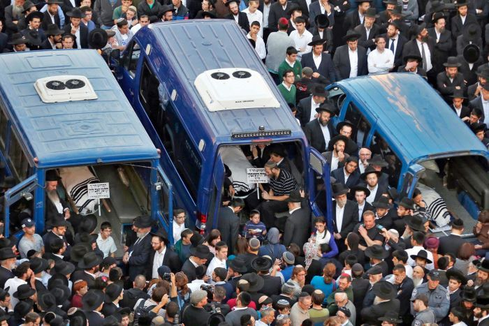Photo: The bodies of Aryeh Kopinsky (C), Calman Levine (L) and Avraham Shmuel Goldberg lie in vehicles during their funeral. (Reuters: Baz Ratner)