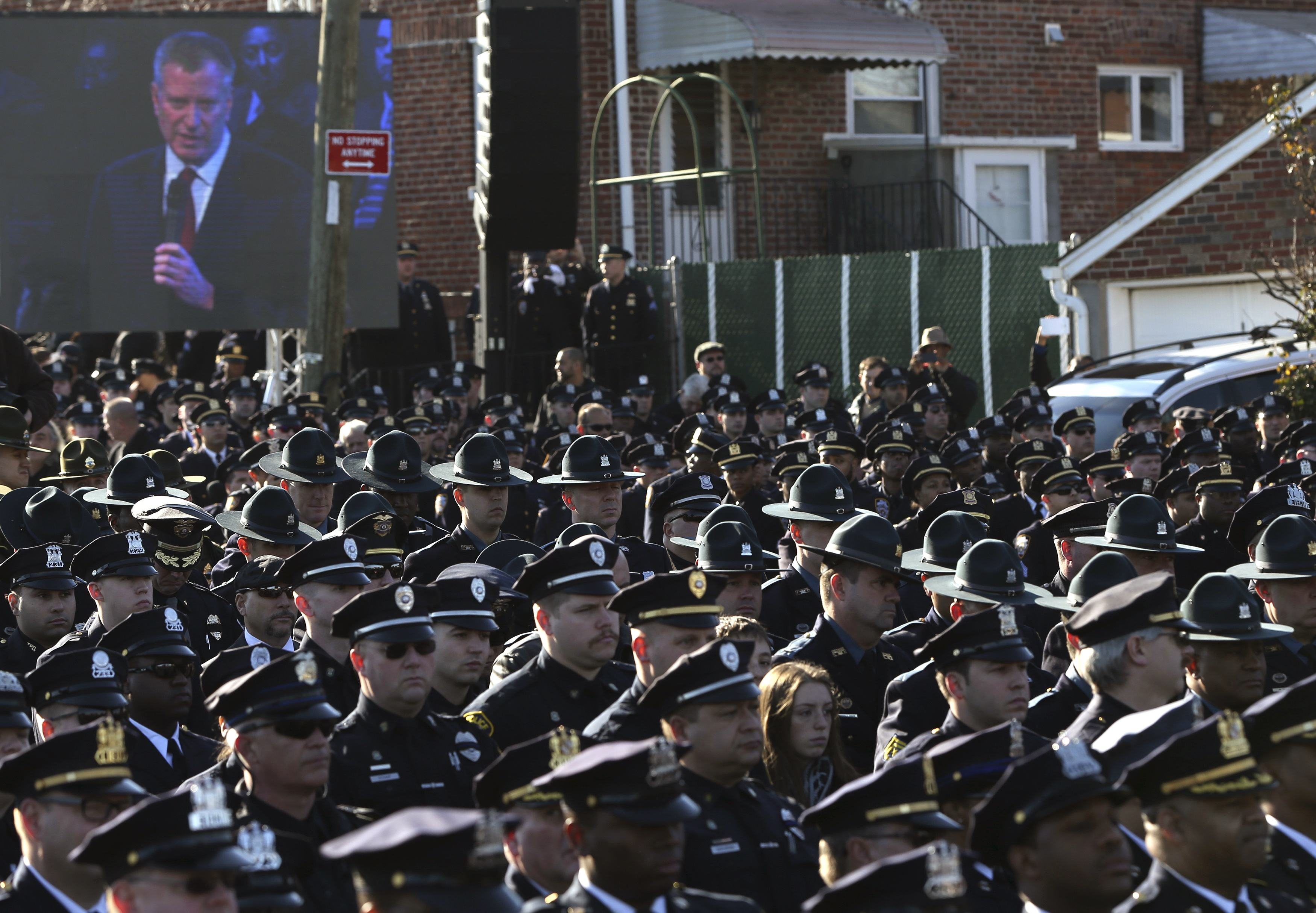 Law enforcement officers turn their backs on a video monitor as New York City Mayor Bill de Blasio speaks during the funeral of slain New York Police Department (NYPD) officer Rafael Ramos near Christ Tabernacle Church in the Queens borough of New York December 27, 2014. Tens of thousands of police and other mourners filled a New York City church and surrounding streets for the funeral on Saturday of one of two police officers ambushed by a gunman who said he was avenging the killing of unarmed black men by police. Singled out for their uniforms, the deaths of Rafael Ramos and his partner Wenjian Liu have become a rallying point for police and their supporters around the country, beleaguered by months of street rallies by protesters who say police practices are marked by racism.   REUTERS/Shannon Stapleton