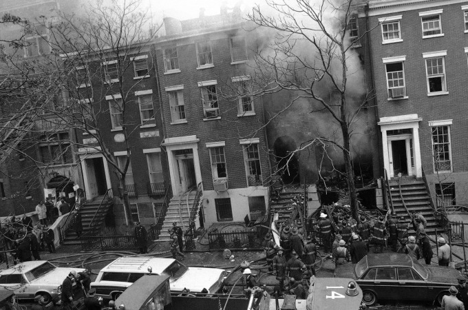 Firefighters work at extinguishing the fire at a residence at 18 West 11th Street in the Greenwich Village section of New York, March 6, 1970, which was rocked by three explosions at midday. The first blast touched off the fire just before noon and two more explosions occurred after the arrival of firefighters at the two-alarm blaze in the four-story townhouse. (AP Photo/Marty Lederhandler)   Weatherman bombing.